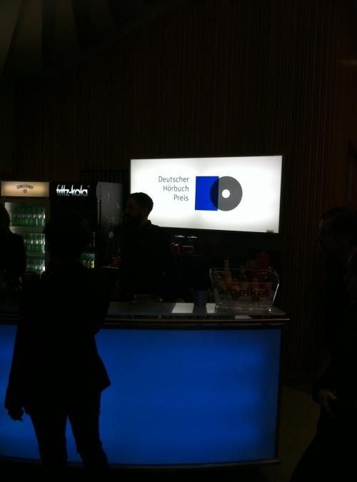 Logo Deutscher Hörbuchpreis über der abgedunkelten Bar im Foyer